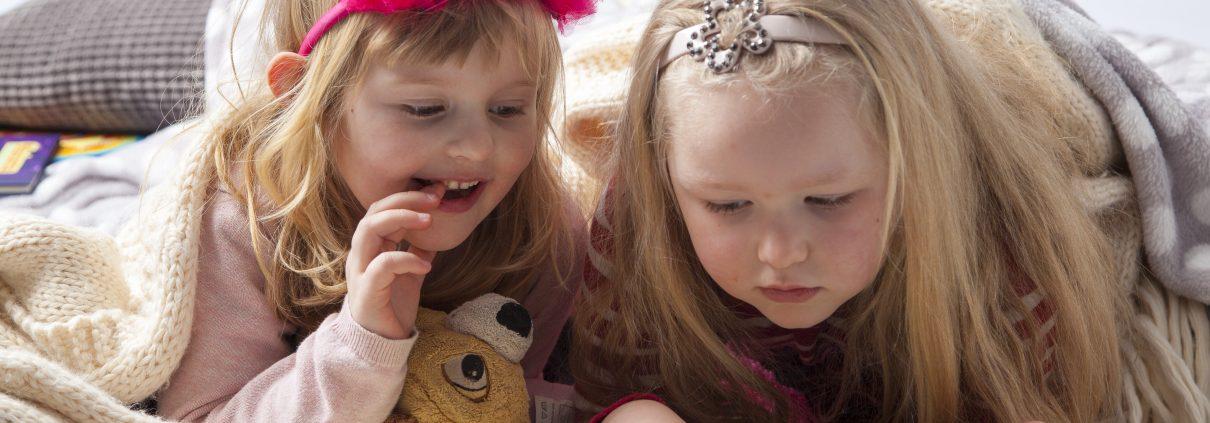 To små pigerslapper af og læser sammen i Musicarma bogen.